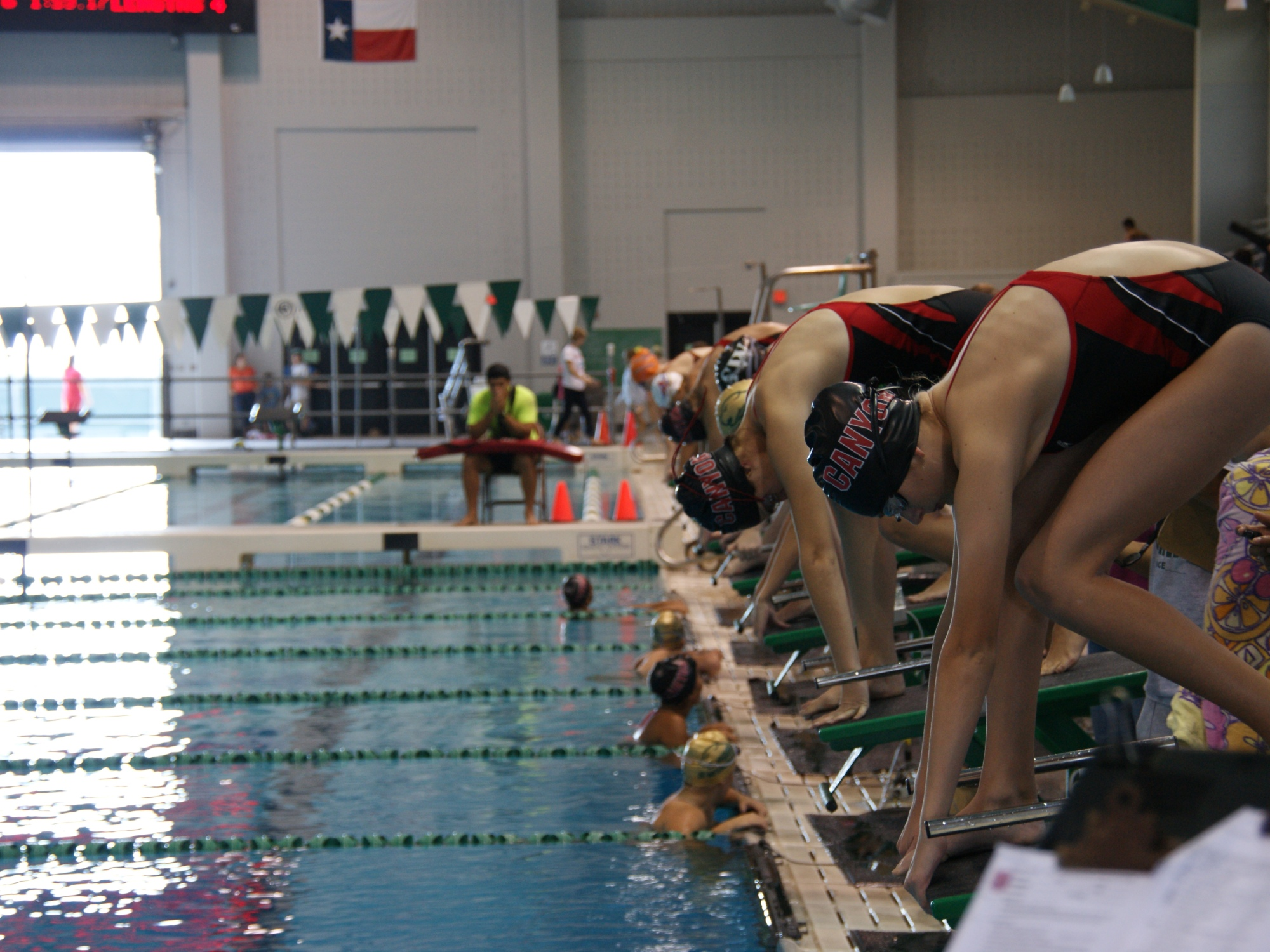 Swimming participants prepare themselves in their swimming position to dive in at Palo Alto's Aquatic Center.