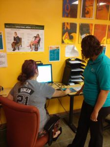 Photo of Veronica Sandoval, peer adviser, helps a student use PAC Connect in the Career Service Center. Photo by Deven Malone.