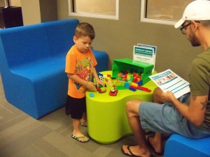 Photo of father and son play during Lego Night.
