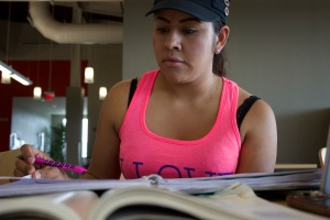 Photo of Reyna Ochoa multitasks with multiple assignments in the Ozuna Library