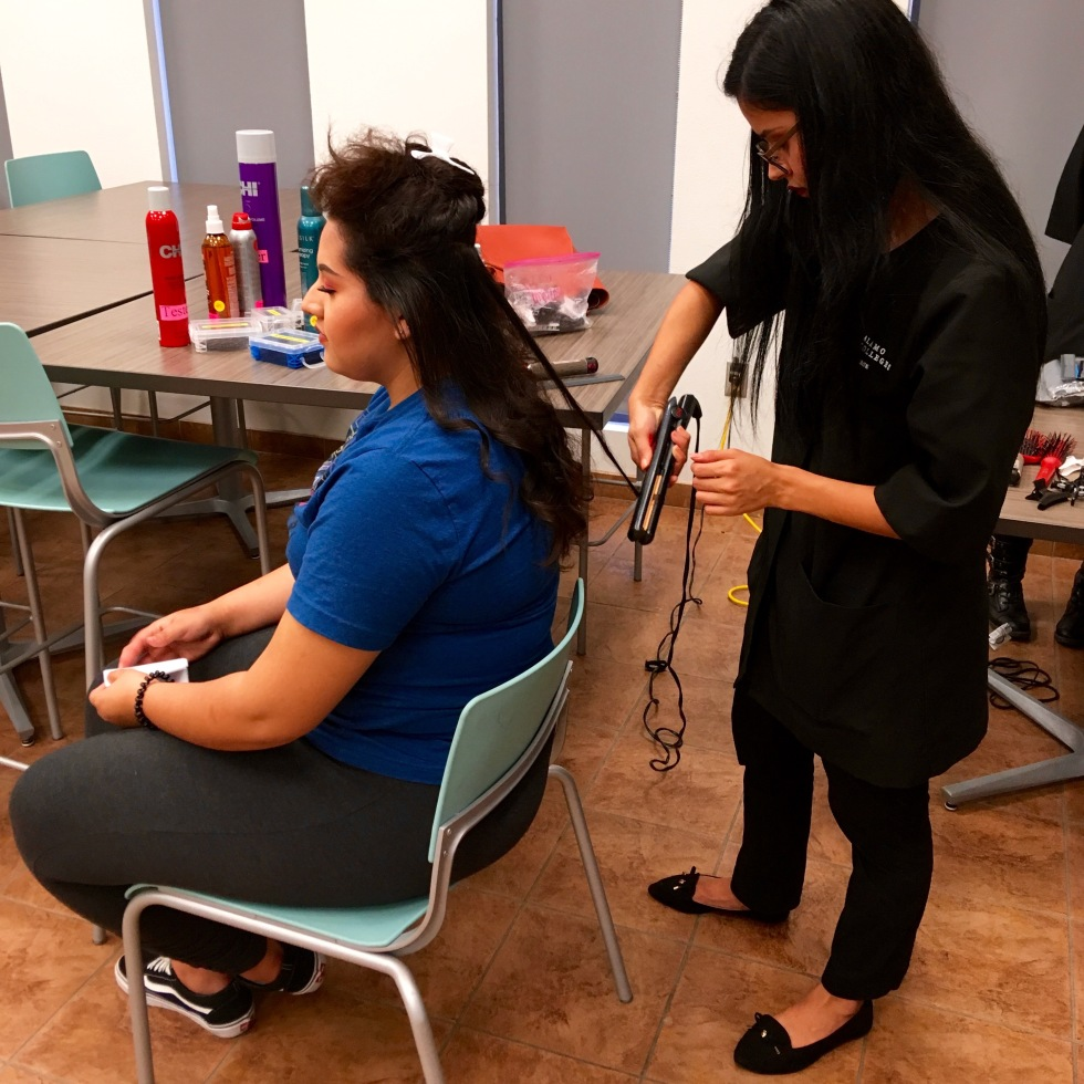Erika Santos, Cosmetology Operator sophomore, works on Irma Martinez's, Public Relations freshman, hair for PAC's America Recycles Day event. Photo taken by Dr. Denise Richter