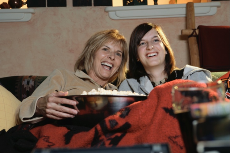 Teen watches a movie happily with their grandmother.