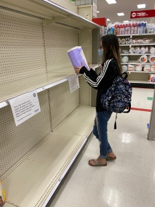 Photo of shopper grabbing last roll of paper towels at the store.