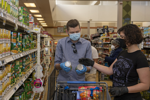 Photo of shoppers taking precautions in the grocery story by wearing facemasks and gloves.