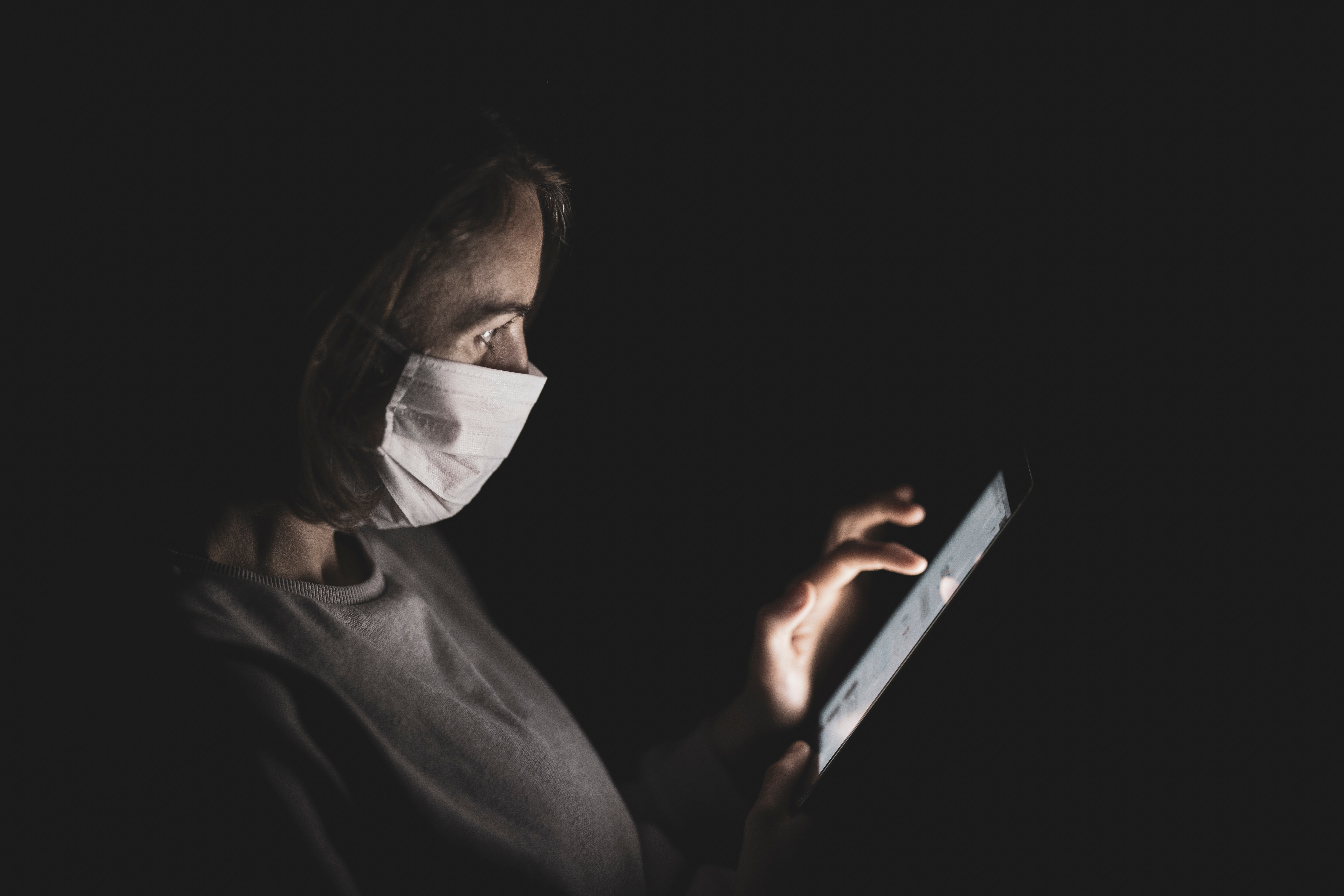 Photo of woman in face mask scrolling on her phone.