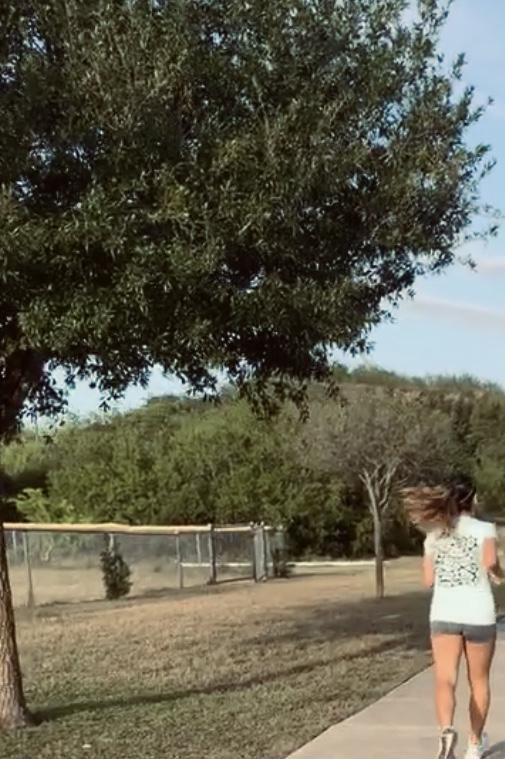 Photo of female jogging through a park.