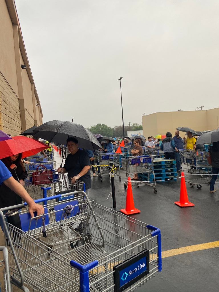 Photo of customers waiting in rain to enter Sam's.